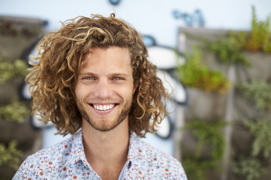 guy with long curly hair and highlights