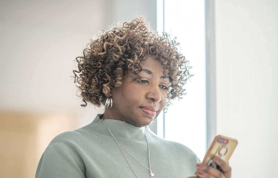 older woman curly hairstyle with highlights